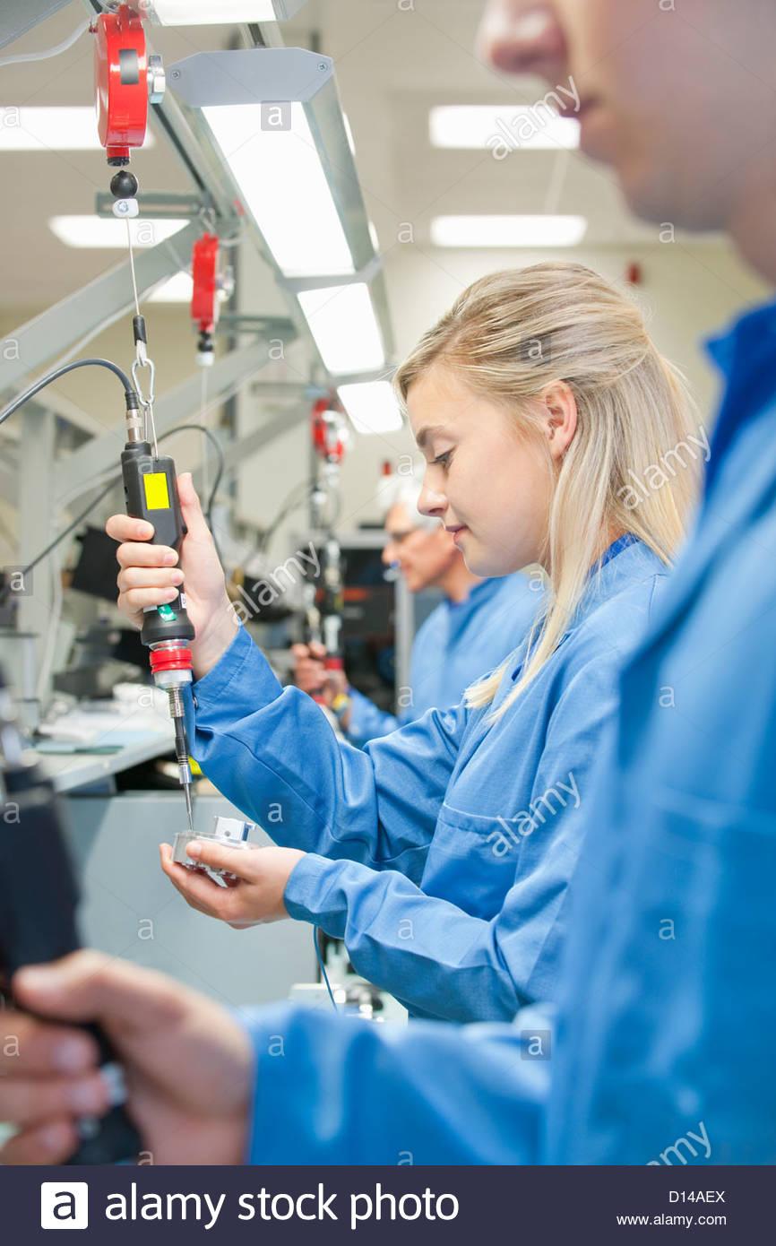À l'aide de tournevis électrique techniciens pour assembler des pièces de machine sur la ligne Photo Stock