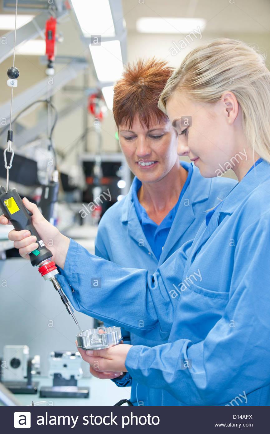 Technicien de formation de superviseur d'utiliser des tournevis électrique pour assembler la partie de Photo Stock