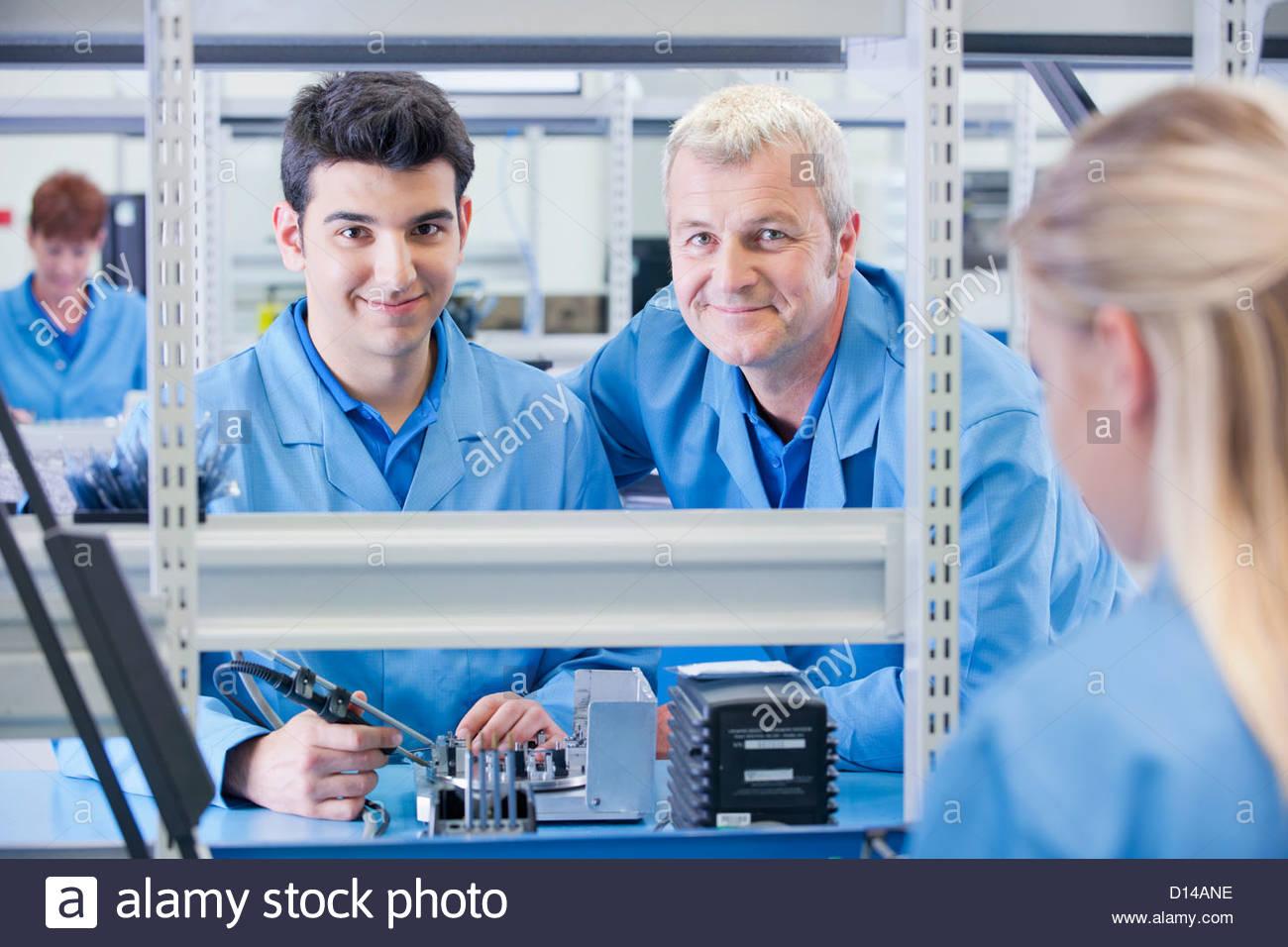 Portrait of smiling superviseur technicien et l'assemblage du circuit dans l'usine de fabrication Photo Stock