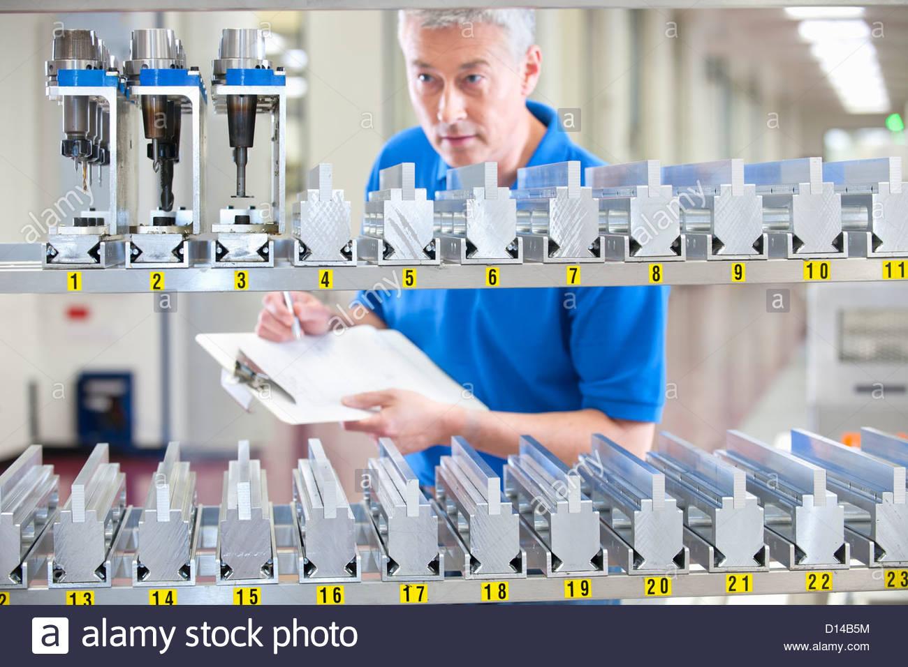 Contrôle de l'inventaire Technicien machine parts in manufacturing plant Photo Stock