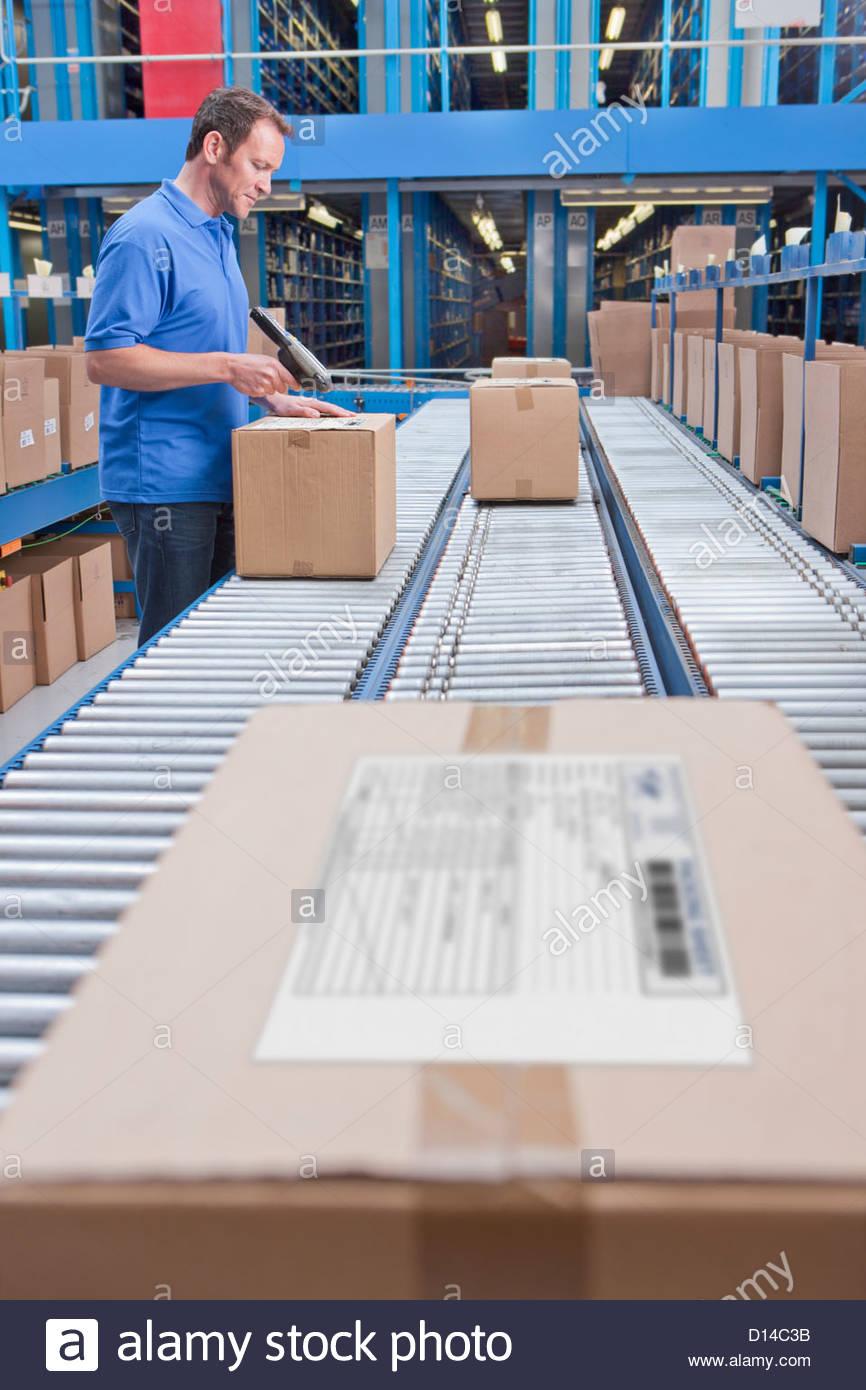 Travailleur avec lecteur de code à barres de balayage sur la courroie du convoyeur en entrepôt de distribution Photo Stock