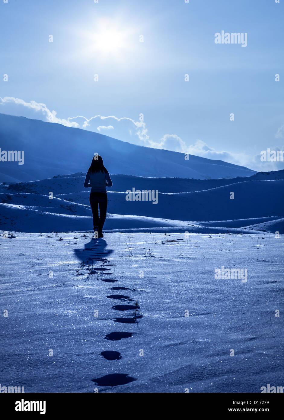 Image de silhouette de femme solitaire au winter mountains, empreintes de pas sur la neige, appréciant la vue Photo Stock