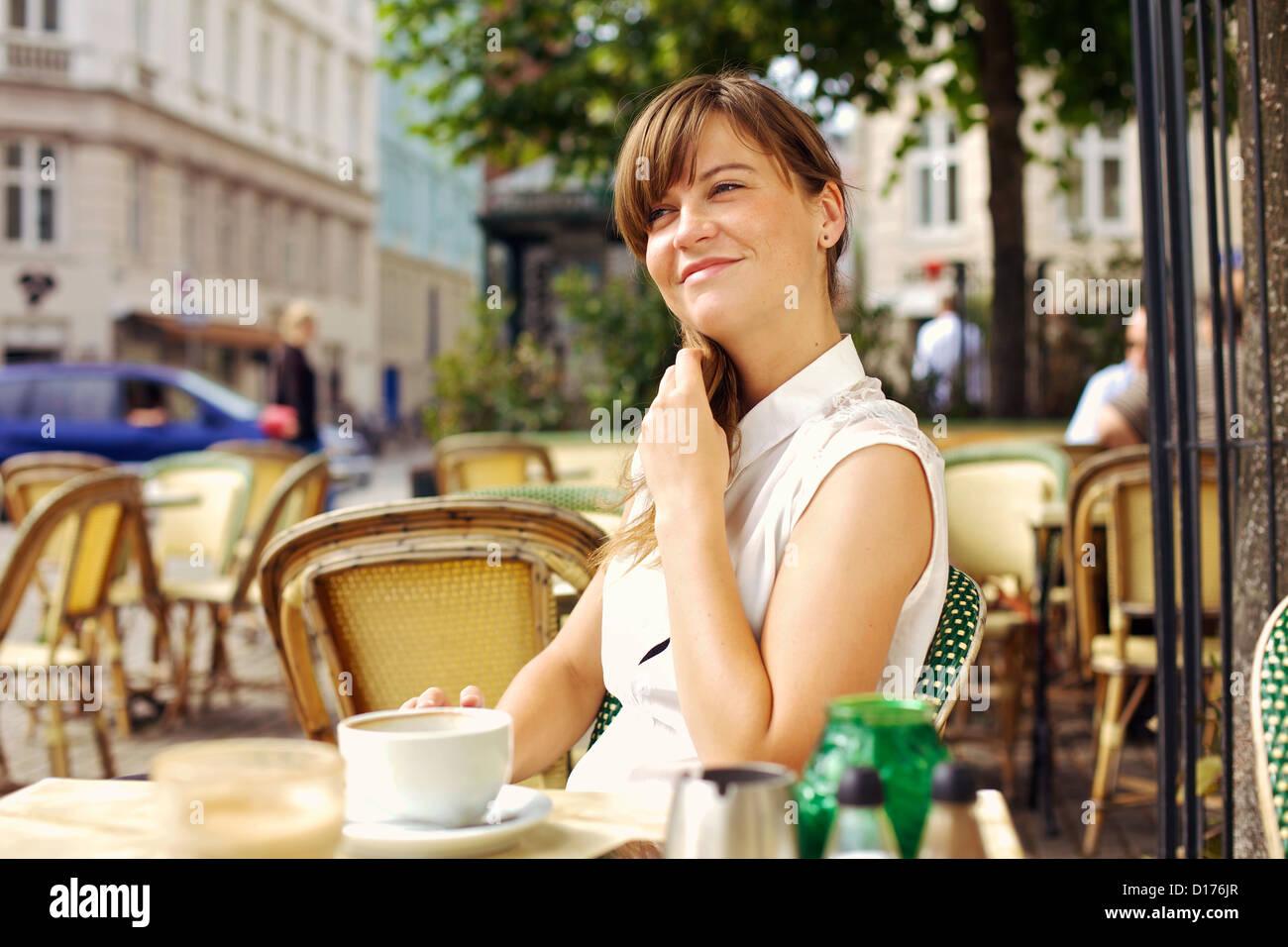 Profitant de la femme agréable matinée avec une tasse de café à l'extérieur, dans un Photo Stock