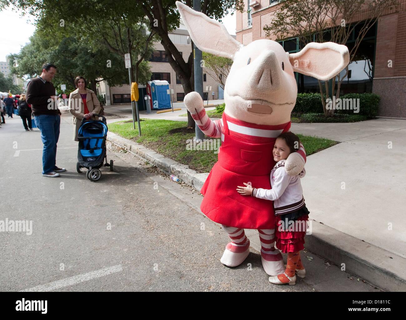 Jeune fille hugs children's book Olivia caractère pendant la fête du livre du Texas à Austin, Photo Stock