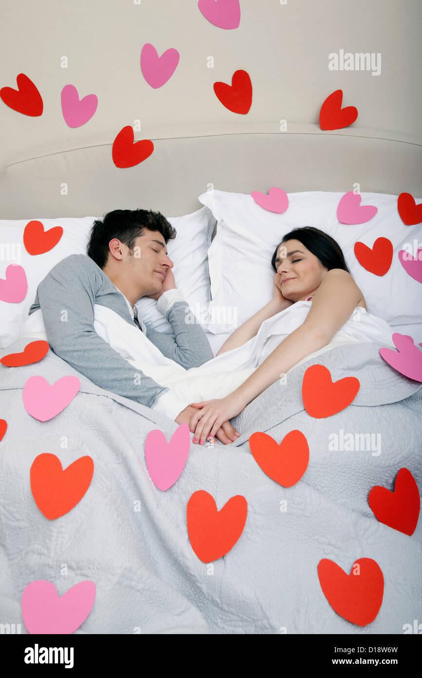 Couple in bed avec cœur les formes sur les draps Photo Stock