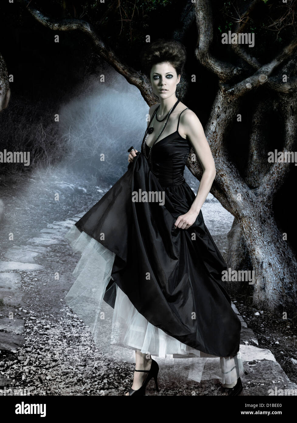 Belle jeune femme portant une robe noire classique dans une sombre forêt mystérieuse. Composé numériquement Photo Stock