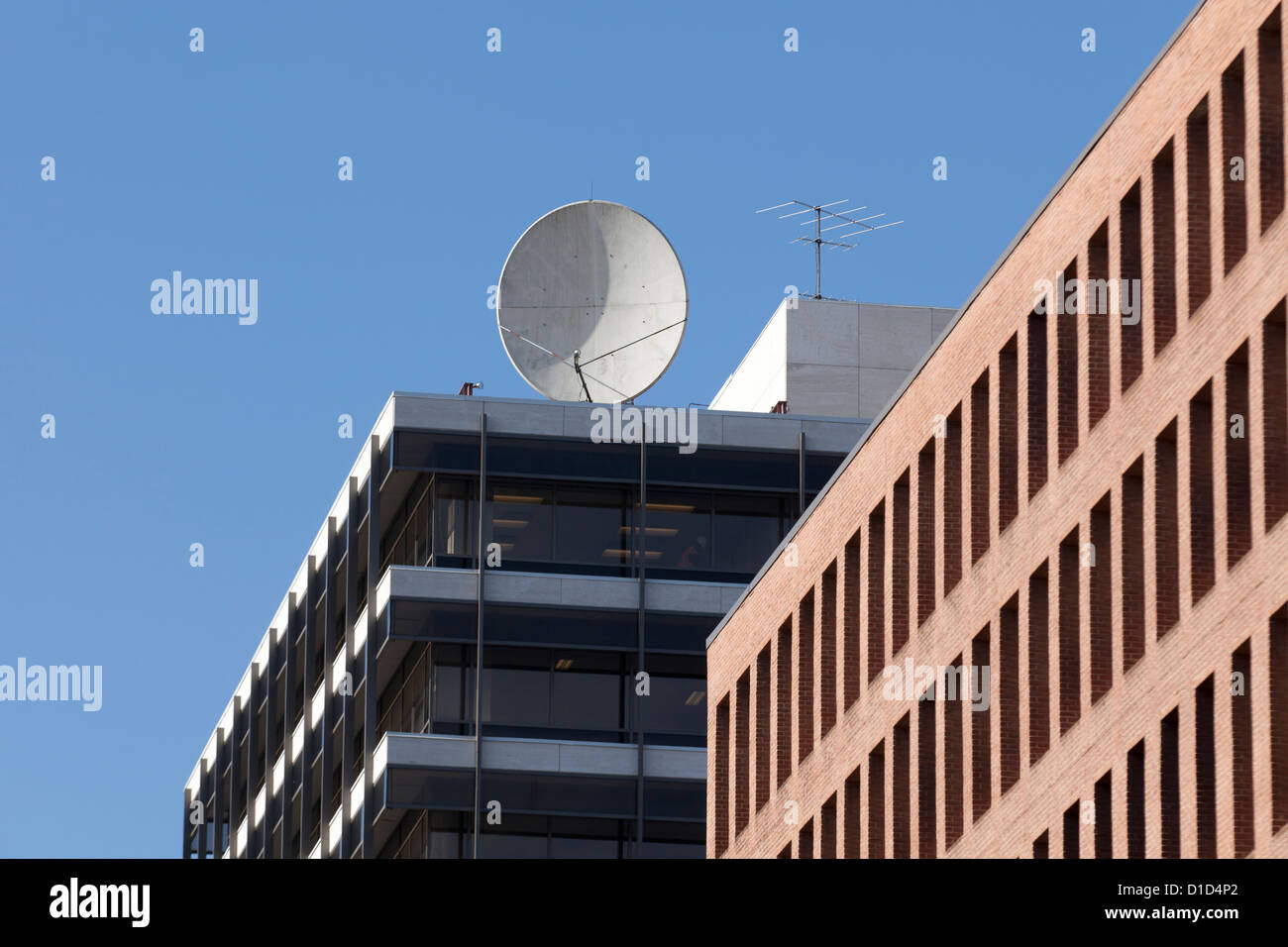 Antenne satellite de communications, au-dessus du bâtiment Photo Stock