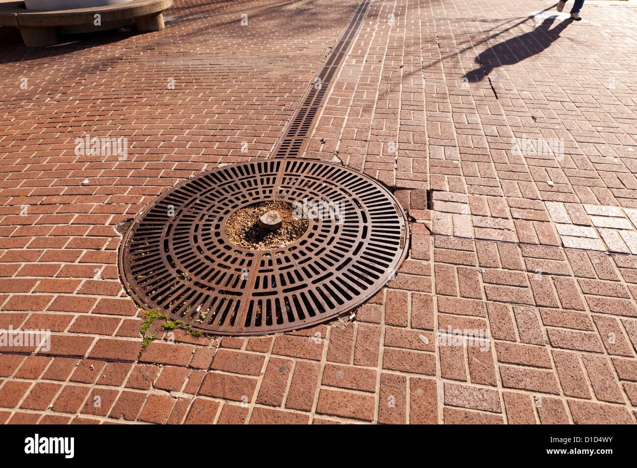 L'ombre de l'homme marche sur la chaussée en brique Photo Stock