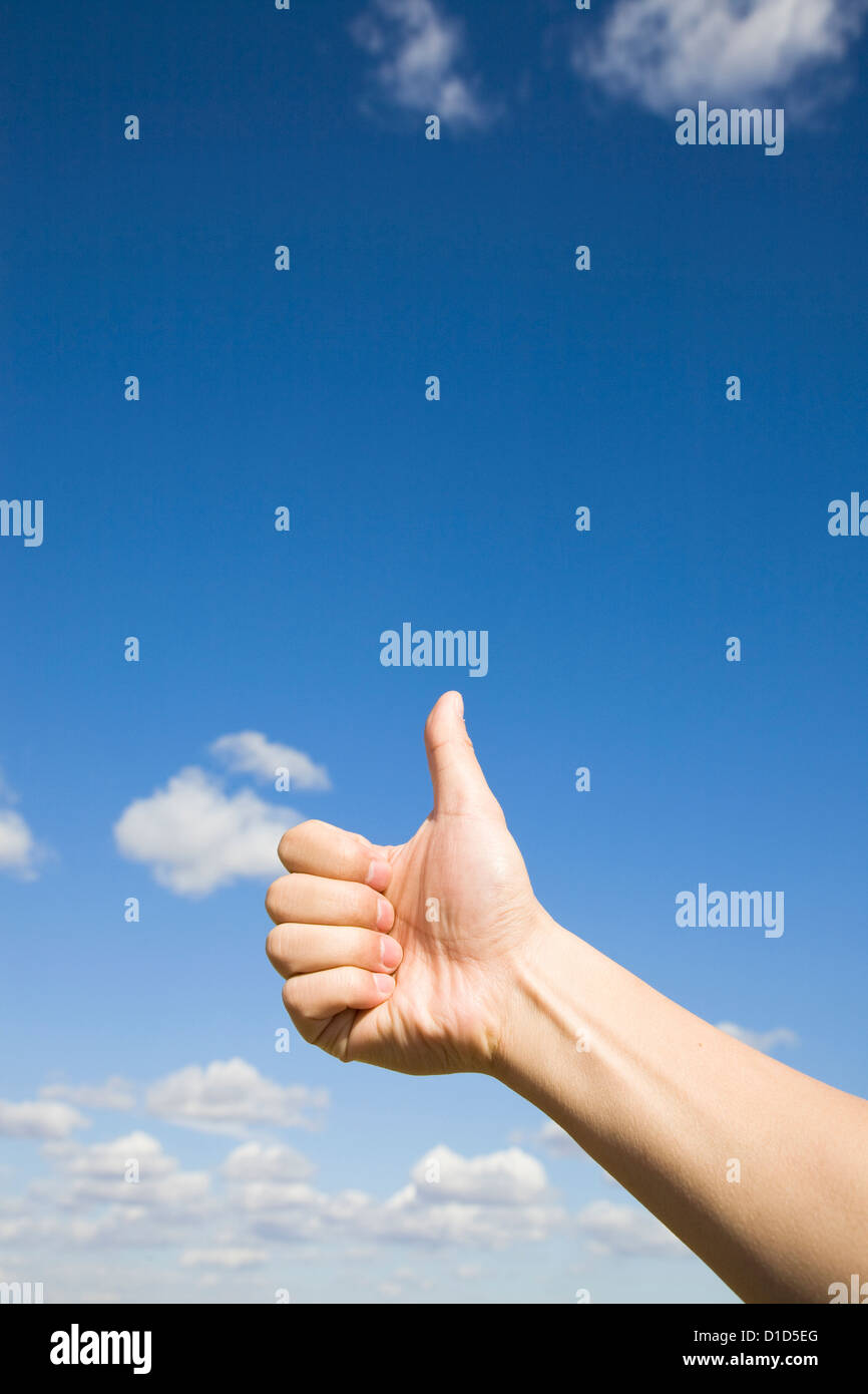 Thumbs up against blue sky Photo Stock