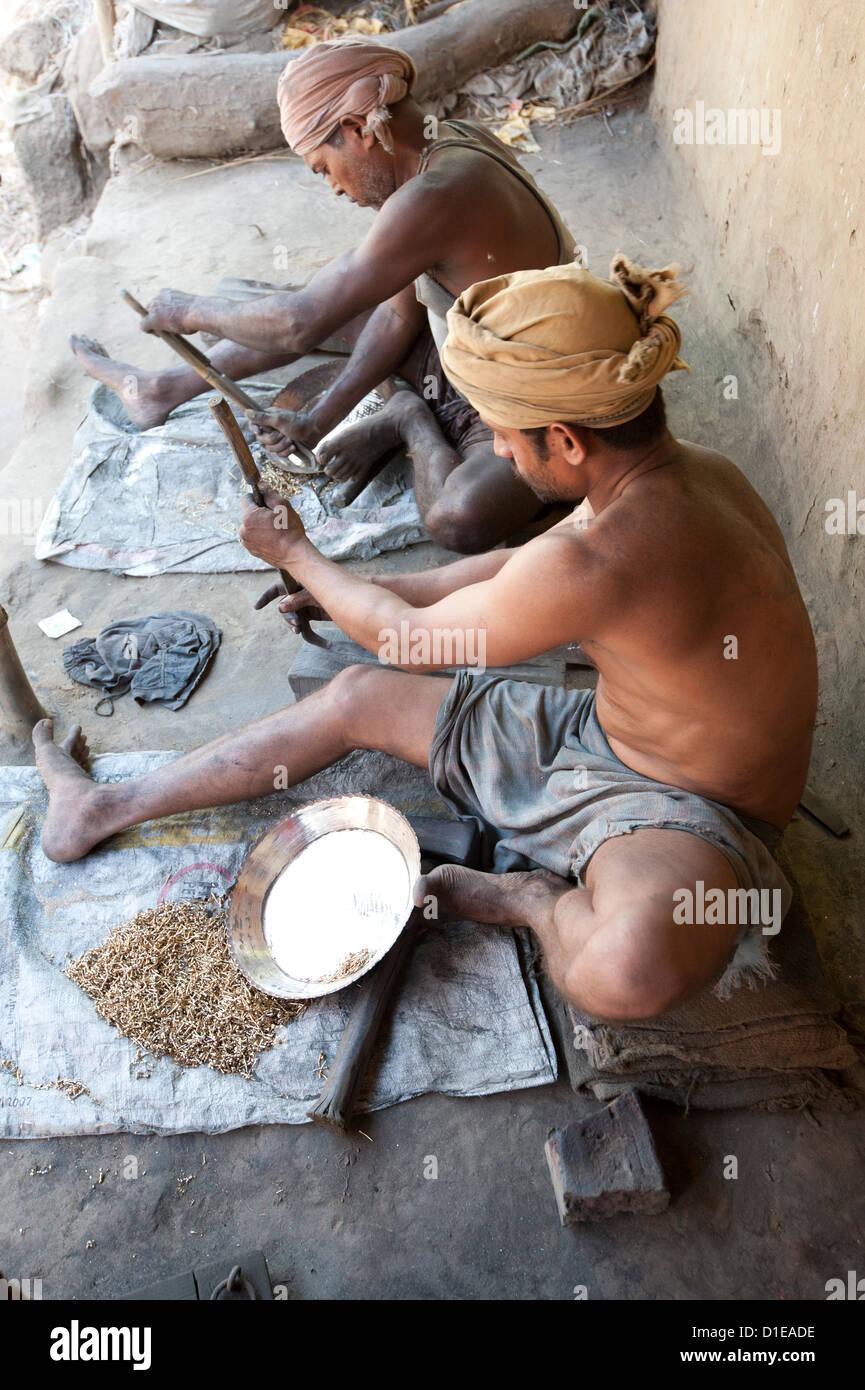 Deux hommes de la surface de lissage des plats en laiton à l'extérieur de la fonderie, Hirapur village, Orissa, Inde, Asie Banque D'Images