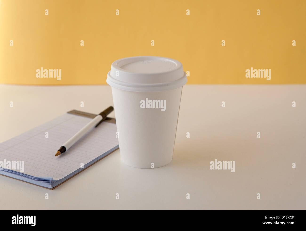 Tasse de café ou de thé est assis sur table ou bureau Photo Stock