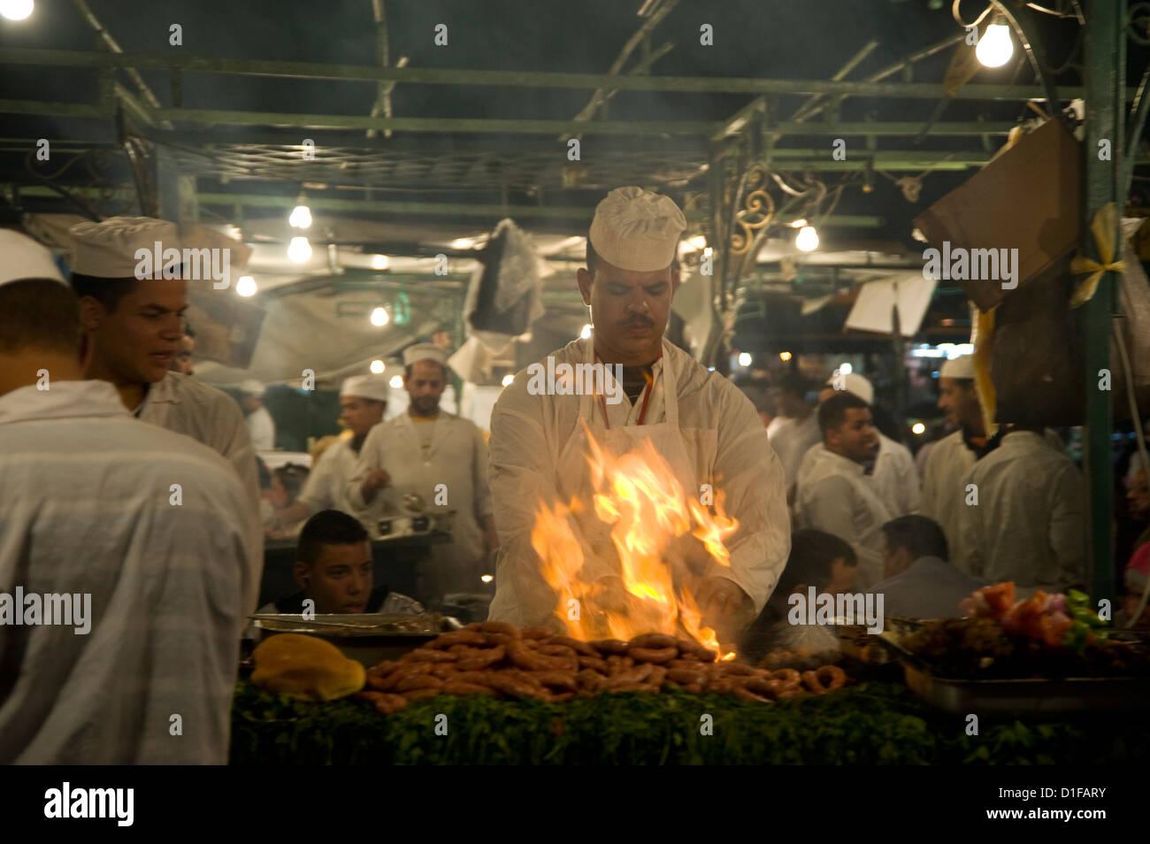 Un chef de la viande à griller des stands de nourriture sur la place principale, la place Jemaa el Fna, à Photo Stock
