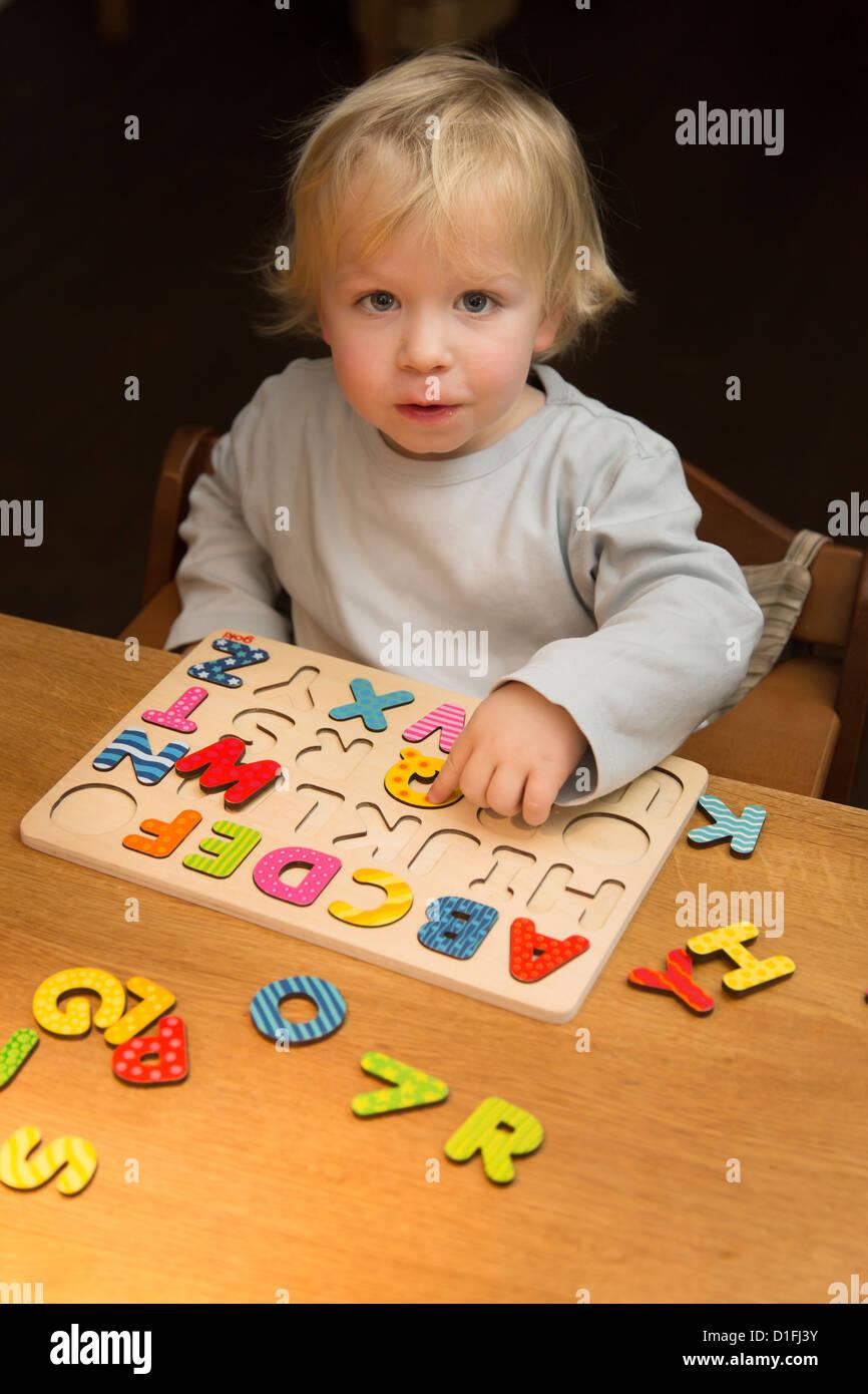 Jeune garçon, 2 ans, joue avec un puzzle ABC, alphabet Photo Stock