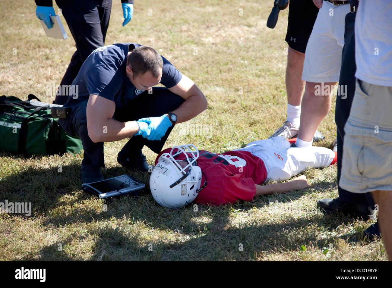 Parler de football blessé paramédic dvd avec une possible commotion. Hauteur Conway's Park St Paul Photo Stock