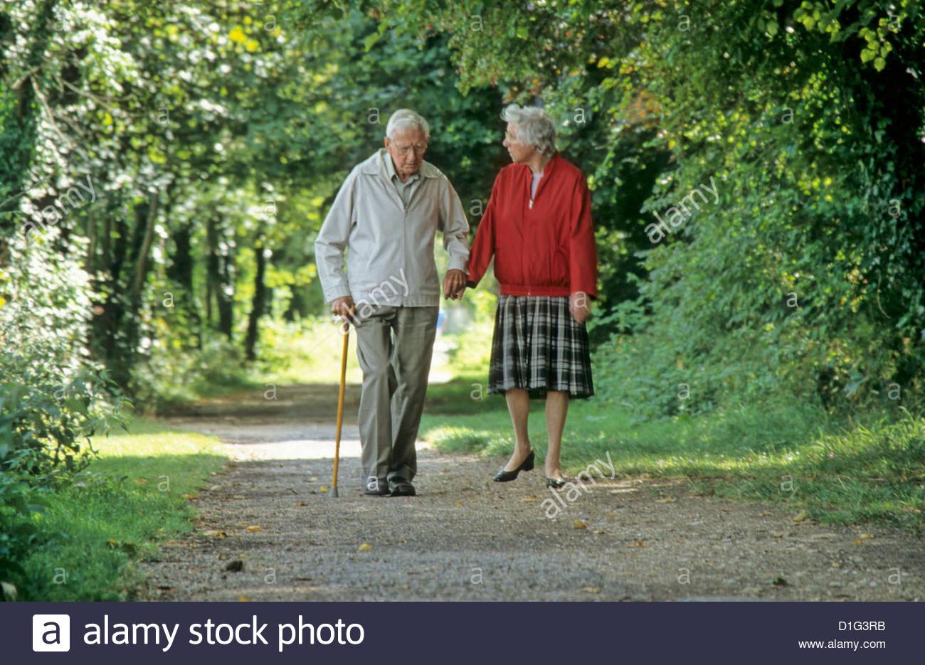 couple de personnes g es b n ficiant d 39 une agr able promenade le long chemin de halage l. Black Bedroom Furniture Sets. Home Design Ideas