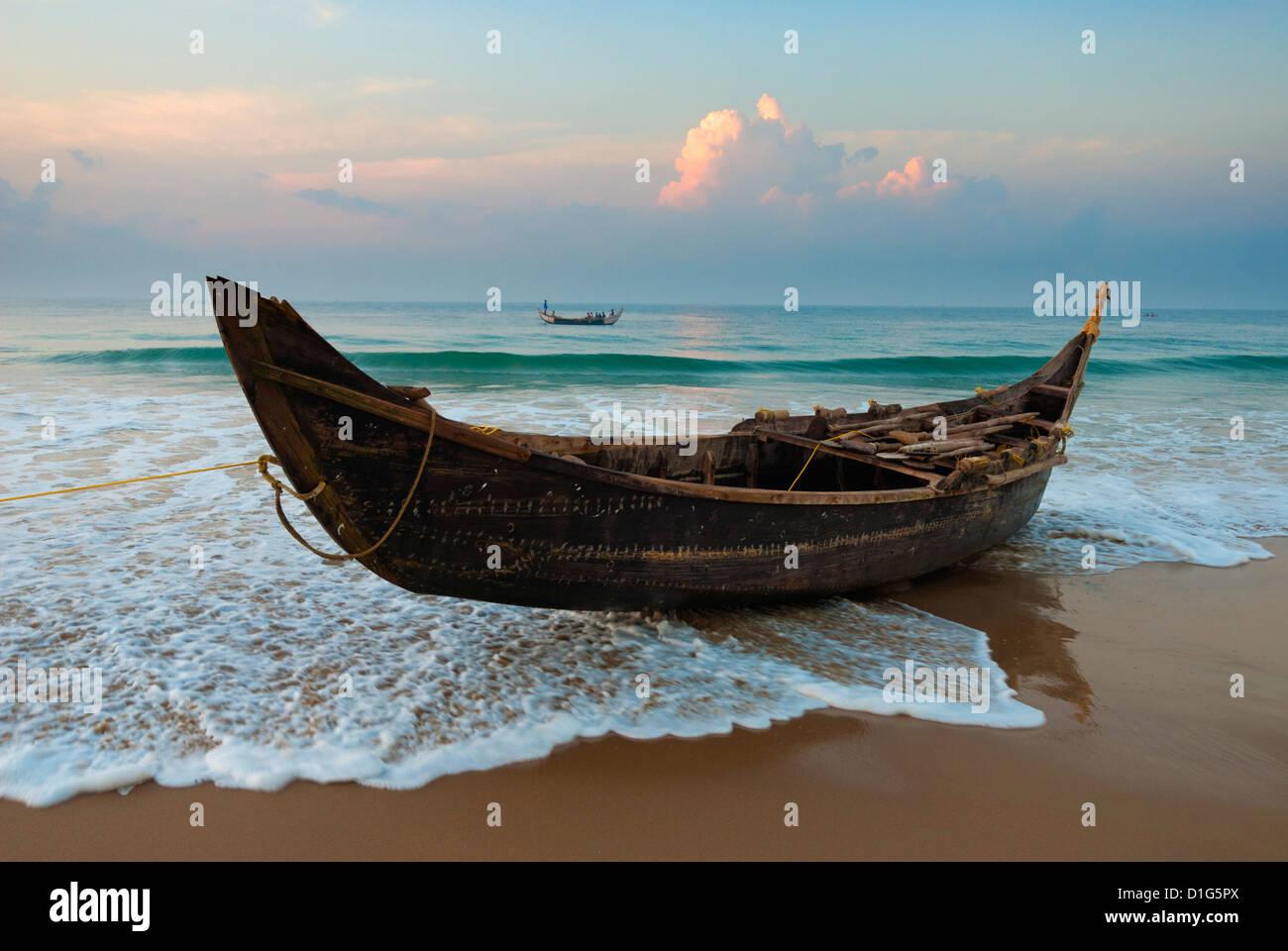Bateau de pêche traditionnel sur la ligne de marée, Chowara Beach, près de Kovalam, Kerala, Inde, Photo Stock