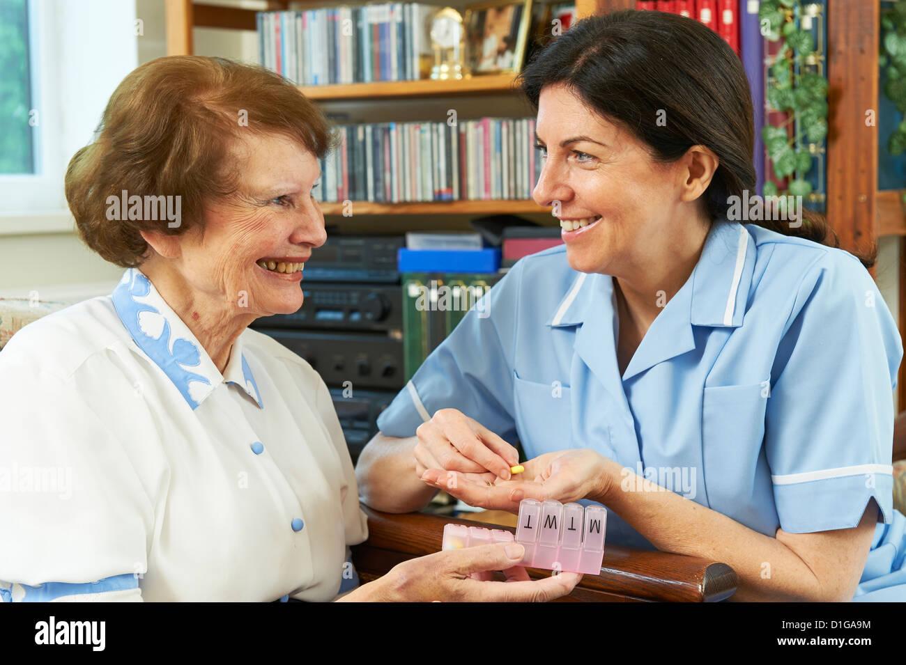 Travailleur de soins aidant les femme avec ses médicaments à la maison Photo Stock