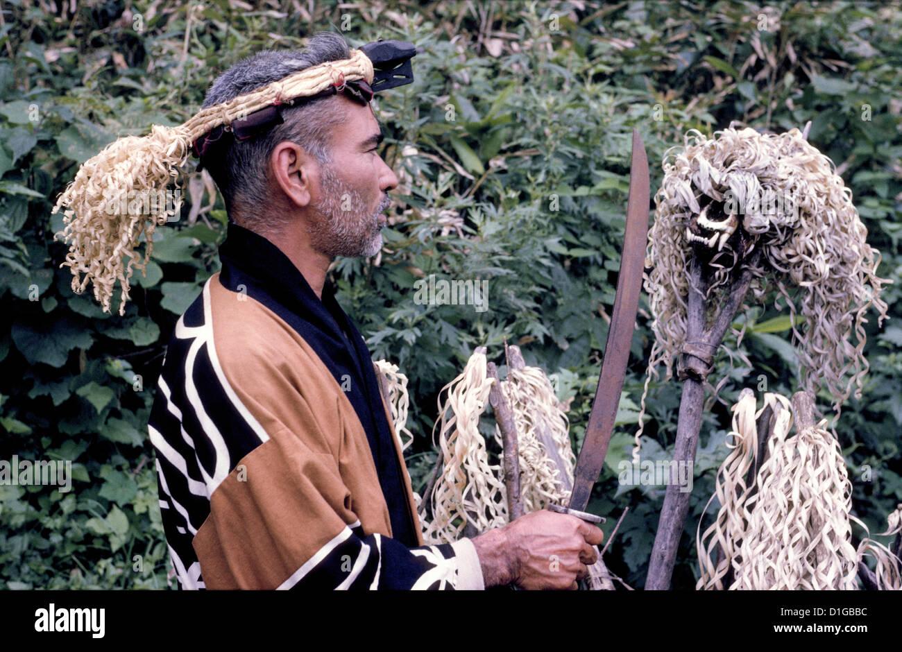 Un homme en costume traditionnel aïnou visite un cimetière orné d'un crâne d'ours sur Photo Stock