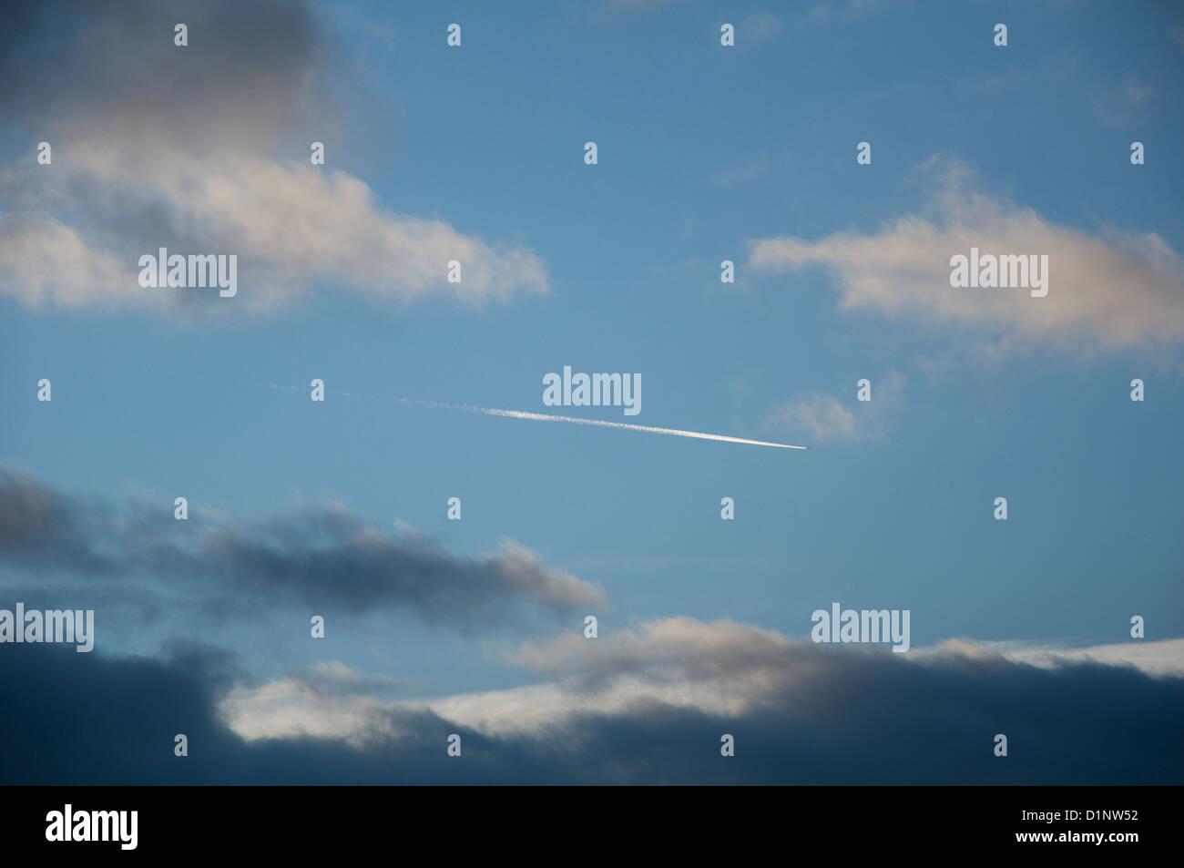 Traînée de condensation d'avion. Comme l'avion se déplace de la gauche dans l'image, Photo Stock