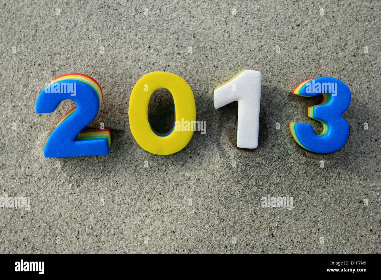 L'année 2012 deux mille treize en bleu et jaune chiffres blancs sur un fond de sable de plage Photo Stock