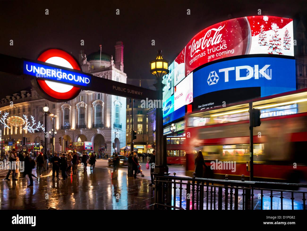 Les gens et London bus rouge sur une longue nuit près de la station de métro Piccadilly Circus inscription Photo Stock