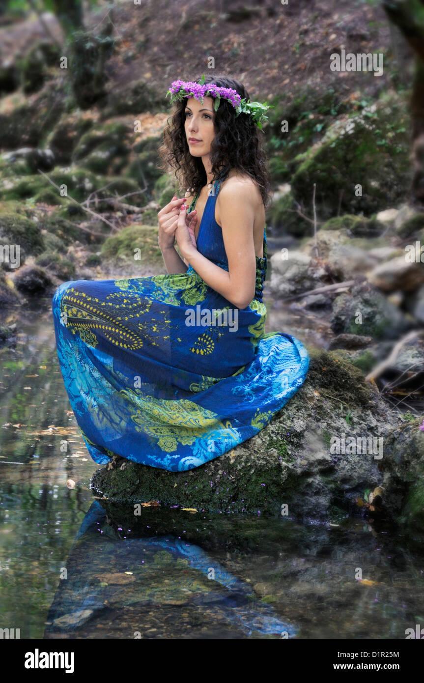 Belle Jeune femme assise au bord de la rivière à la recherche à distance Photo Stock