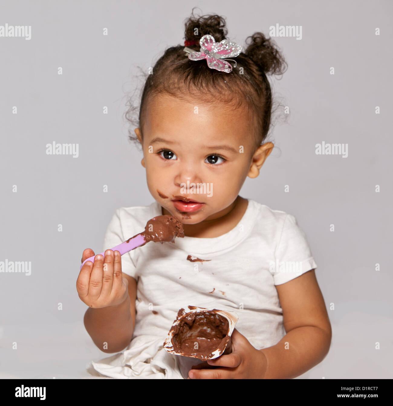 Cute little girl, tout-petit, ce qui fait un désordre de manger un chocolat désert. Photo Stock