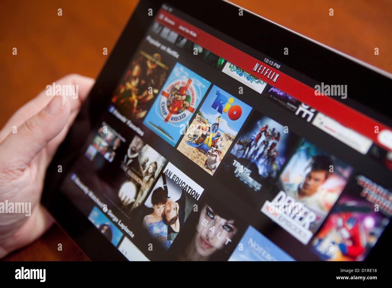 Une femme utilise l'app Netflix sur un iPad 4. Netflix, Inc. est un fournisseur américain de services sur Photo Stock