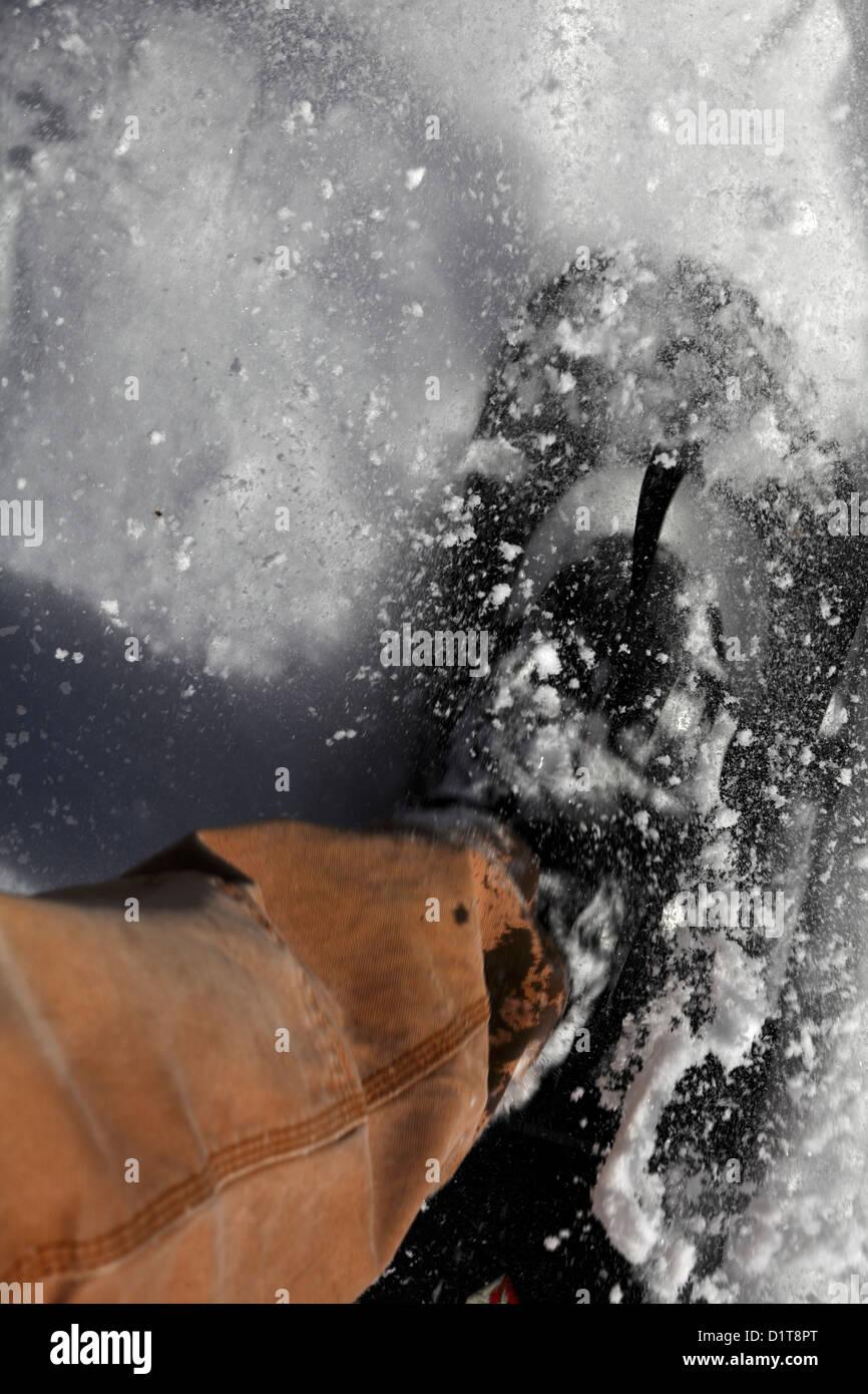 Porter des coups de pied en raquettes de neige les particules. Photo Stock