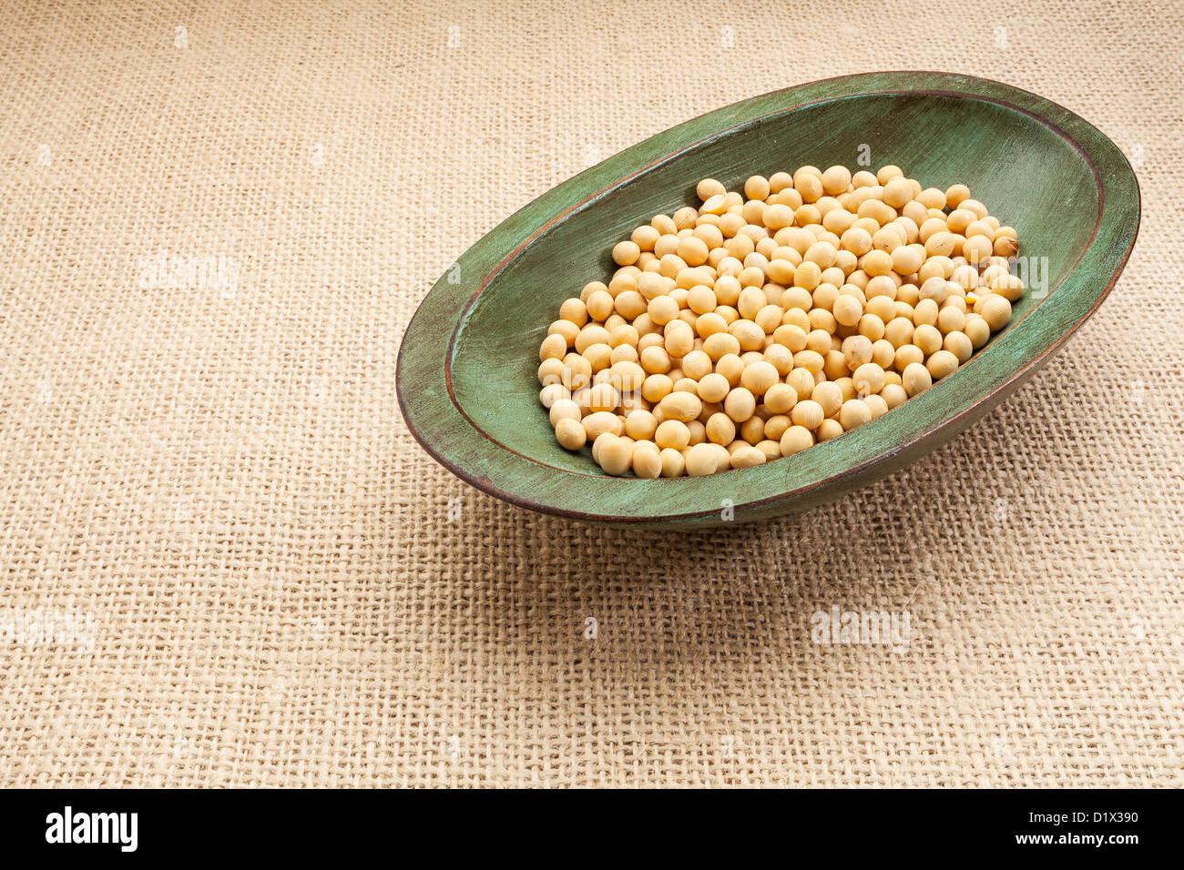 Le soja dans un bol en bois rustique toile de jute contre Photo Stock