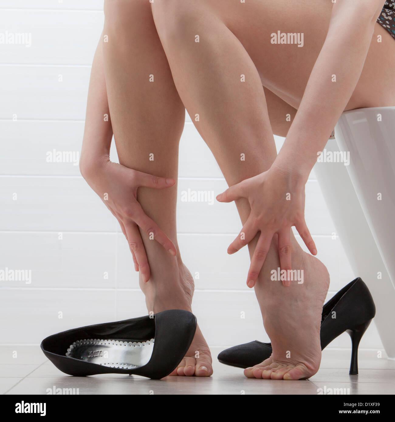 Femme assise sans chaussures frotte les chevilles Banque D'Images