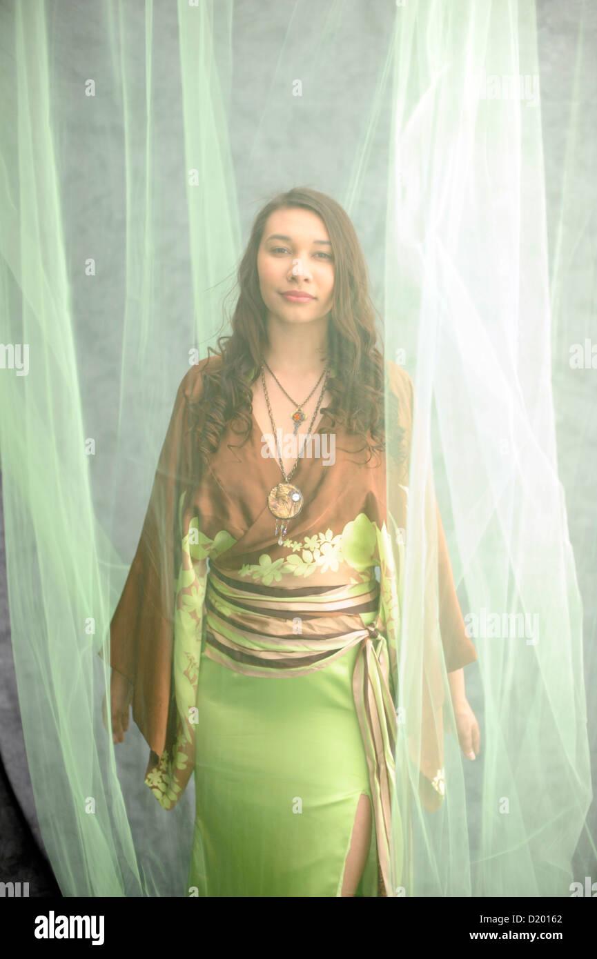 Belle jeune femme habillée d'une robe printemps kimona moderne dans des tons vert voilée de tule. Photo Stock