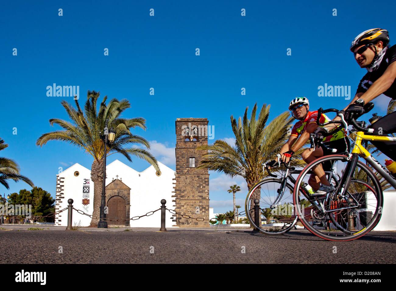 Cycliste passe l'église Iglesia Nuestra Señora de La Candelaria, Olvia, Fuerteventura, Îles Canaries, Photo Stock