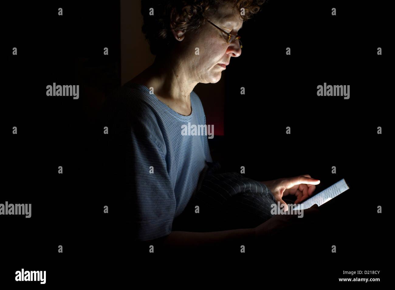 Femme lisant un livre sur un e-reader tout en s'asseyant sur son lit Photo Stock