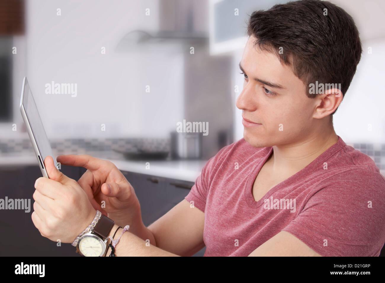 Jeune homme à l'aide d'une tablette numérique, regarder l'écran ou moniteur. Situé Photo Stock