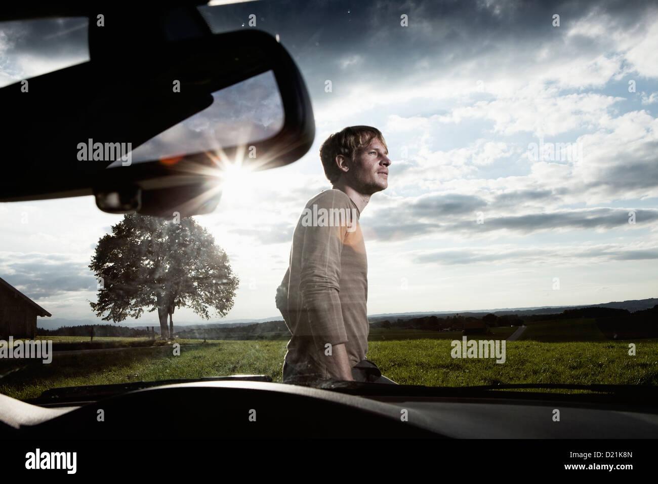 Allemagne, Bavière, Mid adult man standing en voiture Photo Stock