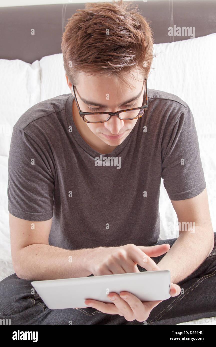 Jeune homme portant des lunettes à la recherche à l'écran de sa tablette numérique, assise Photo Stock
