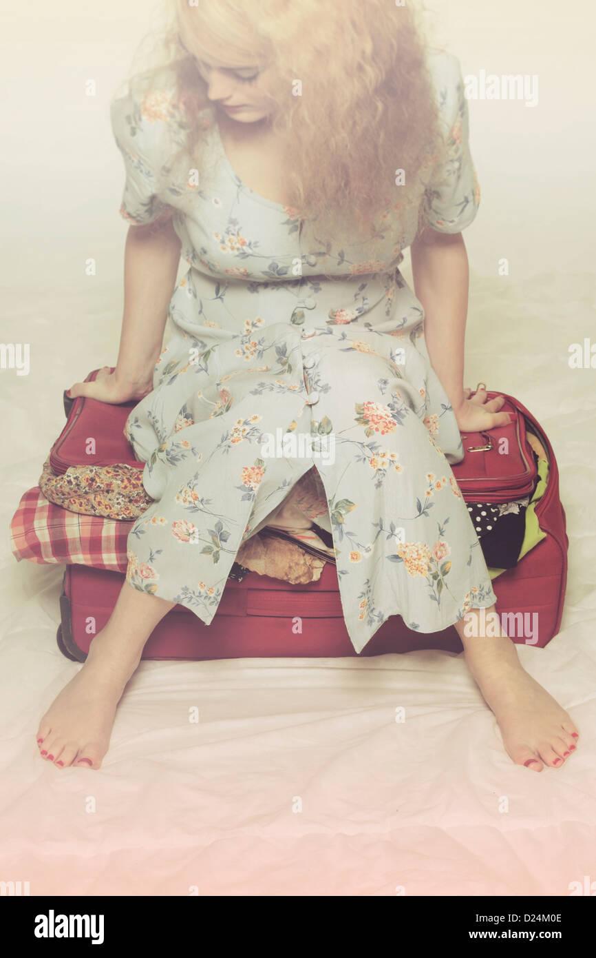 Une femme essaie de fermer une valise par assis sur elle Photo Stock