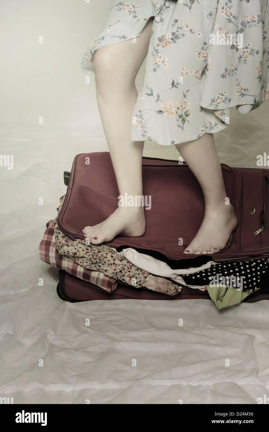 Une femme essaie de fermer une valise à ses pieds Photo Stock