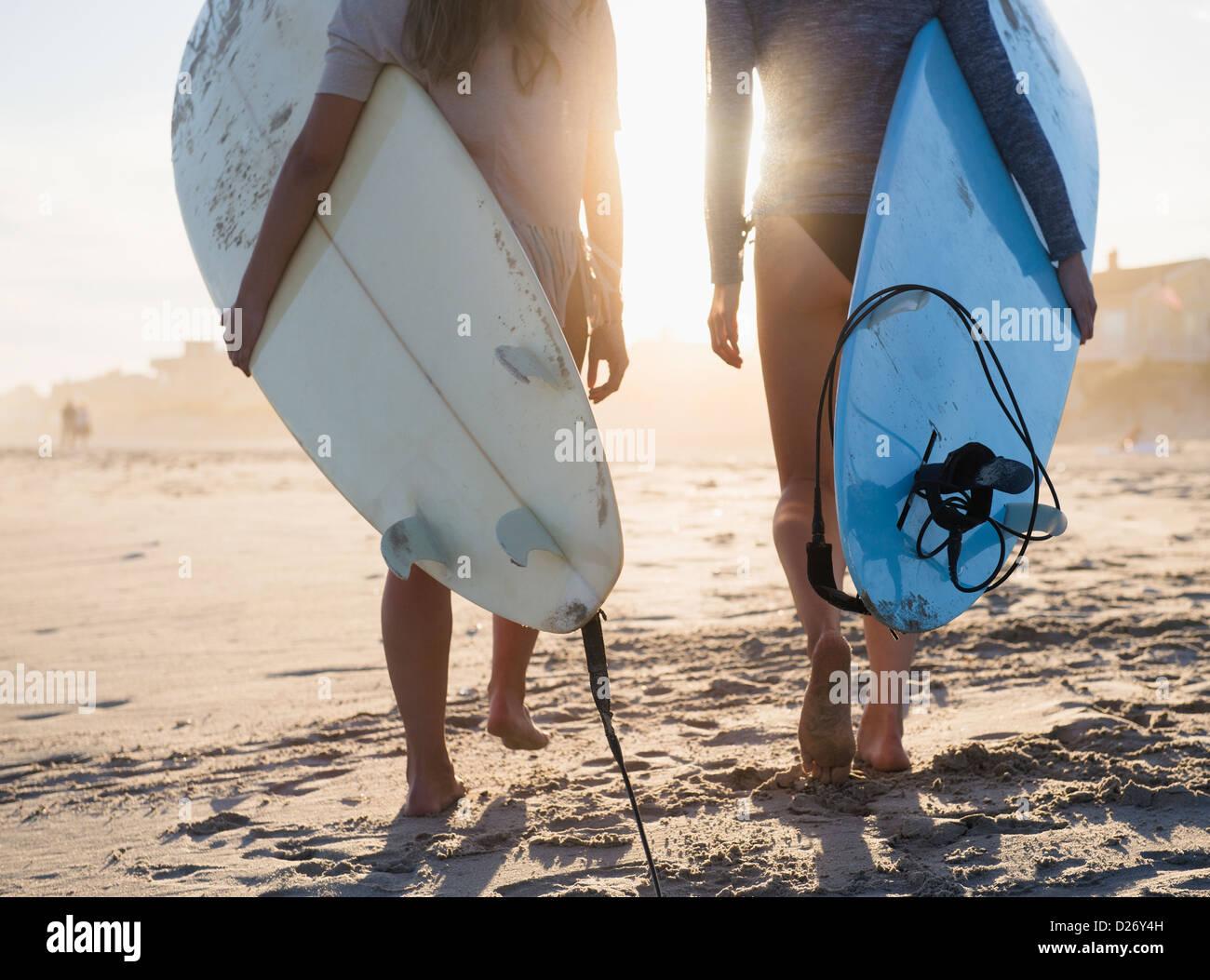 USA, New York State, Rockaway Beach, deux femmes surfers walking on beach Photo Stock