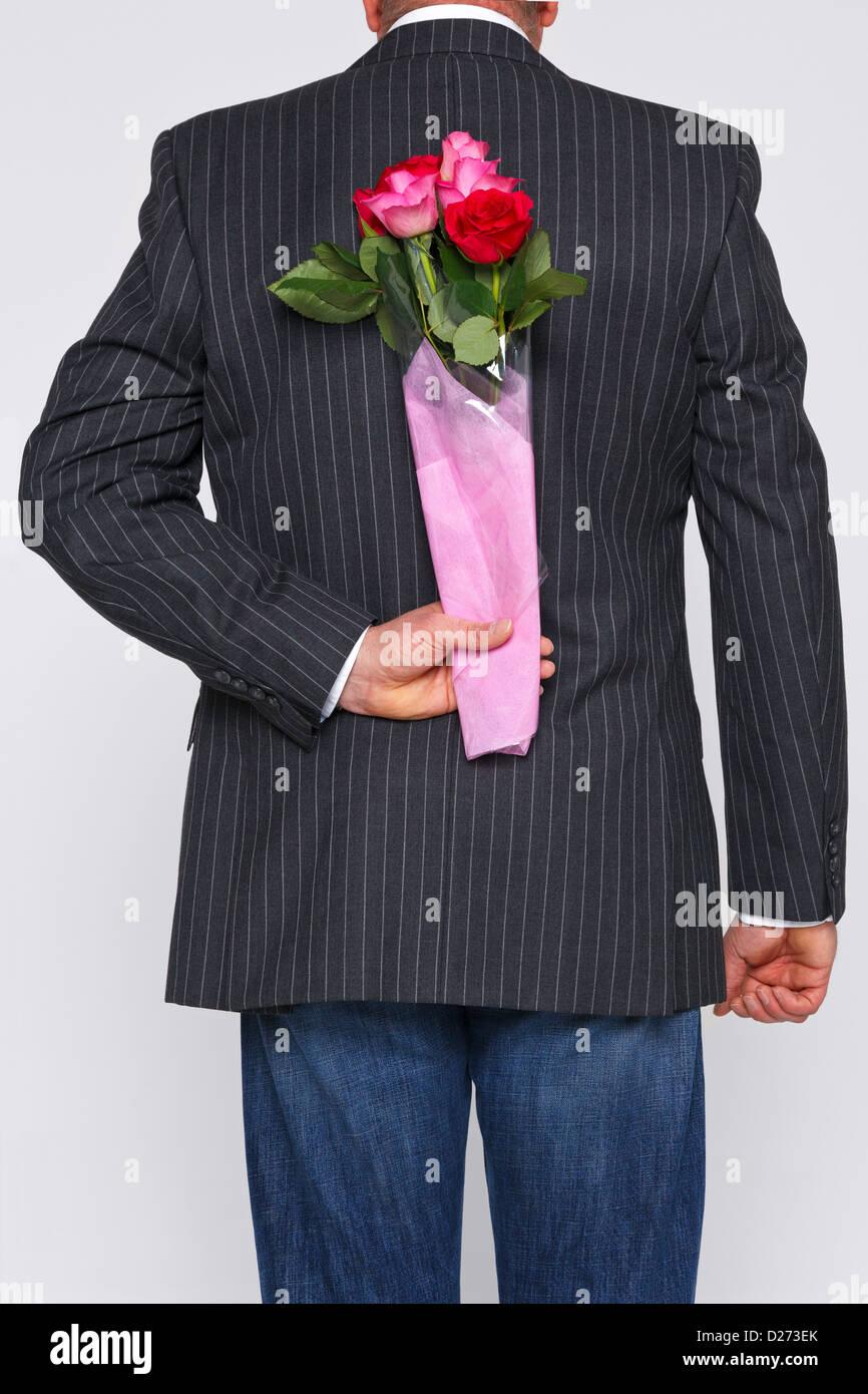 Un homme avec un bouquet de roses derrière son dos, les fleurs sont une surprise pour quelqu'un. Photo Stock
