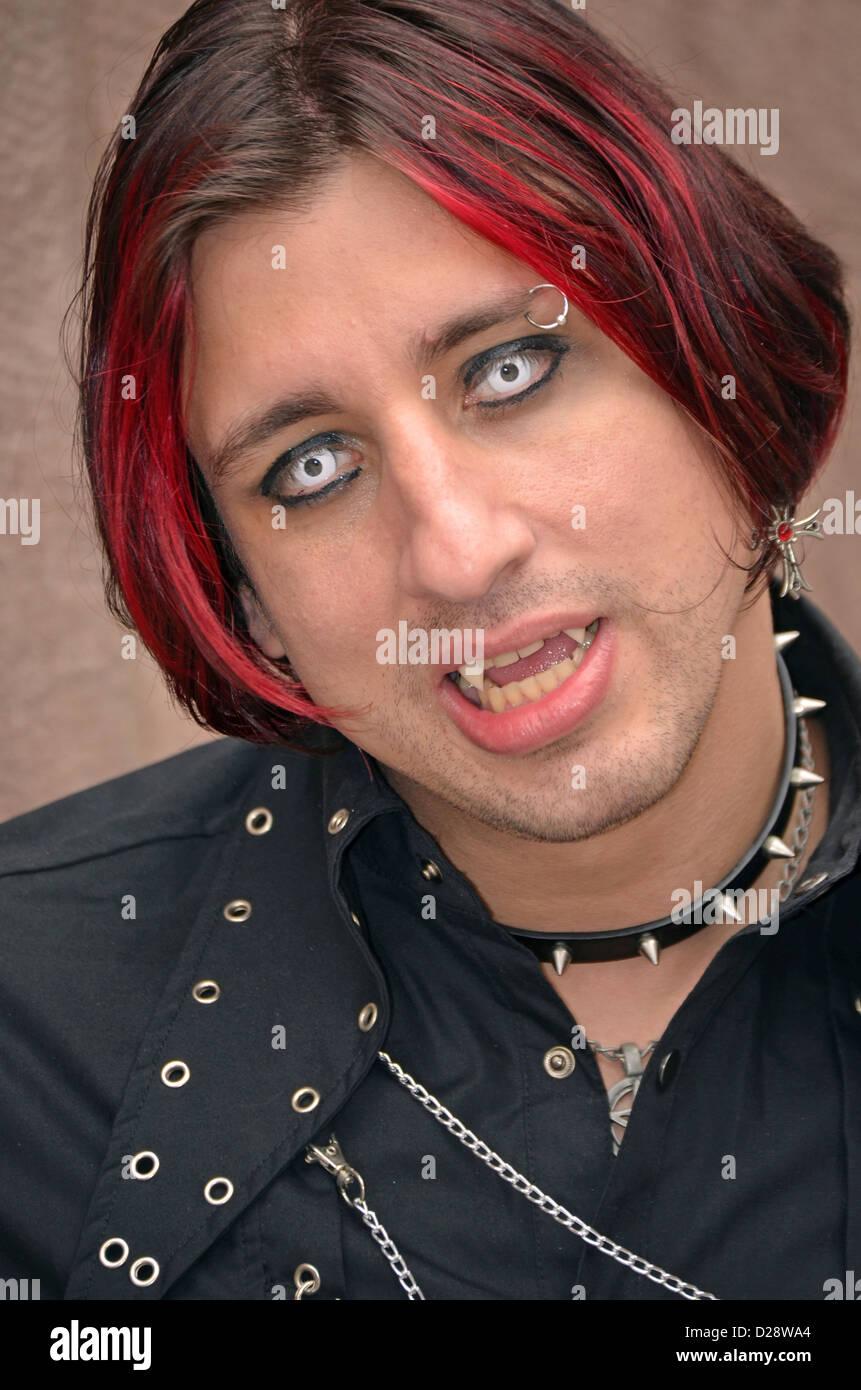 Portrait d'un homme en costume vampire goth punk avec les dents, les cheveux rouges et les costumes des lentilles Photo Stock