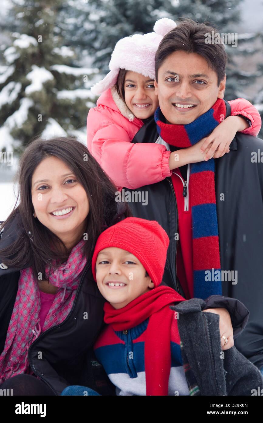 Une belle East Indian parents jouer avec ses enfants dans la neige. Photo Stock