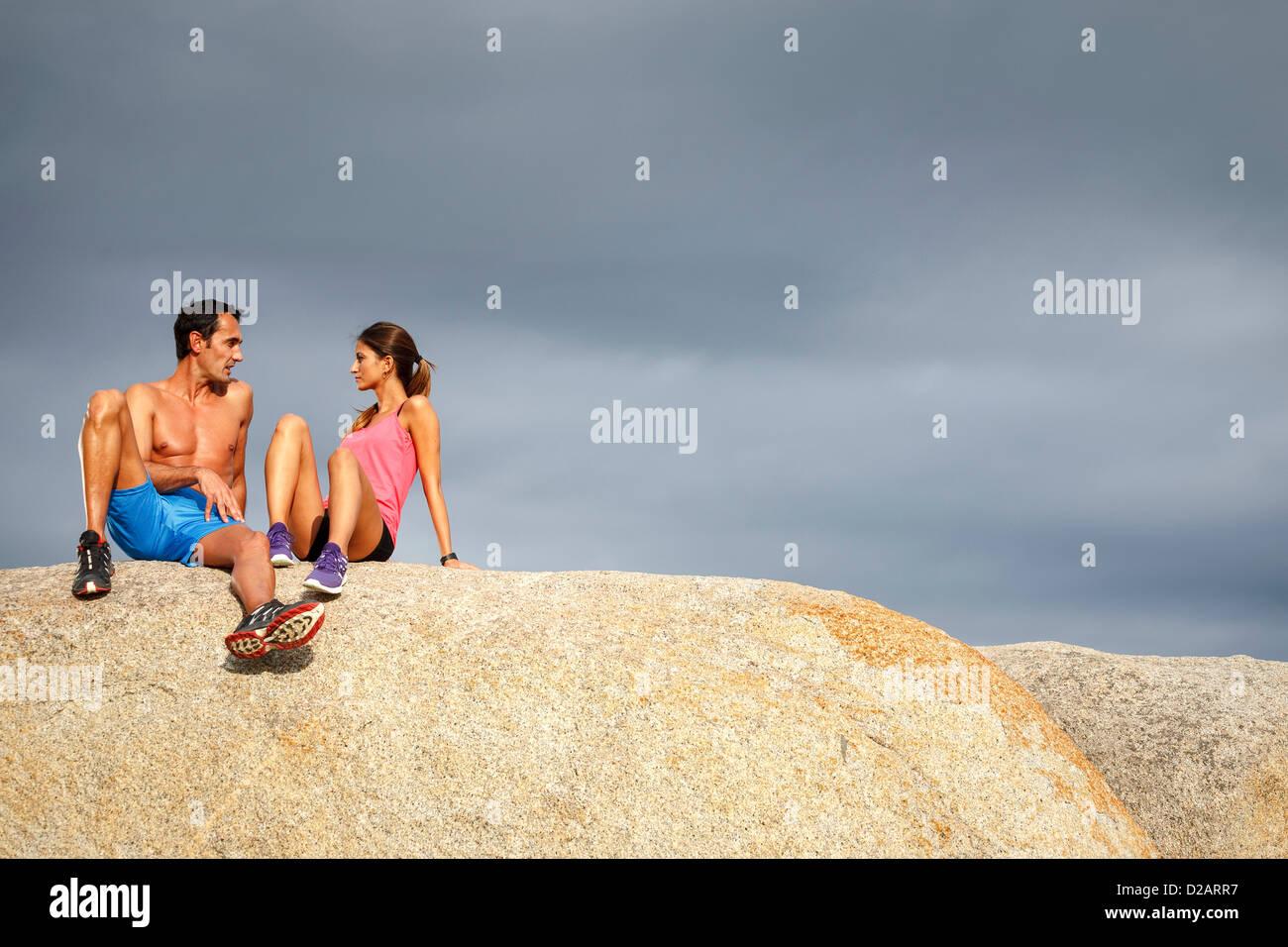 Couple sitting on boulder Photo Stock