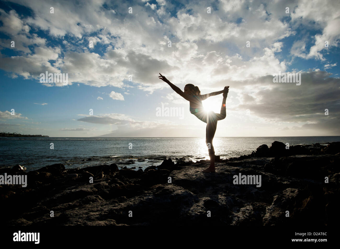 Woman practicing yoga on rock formation Photo Stock
