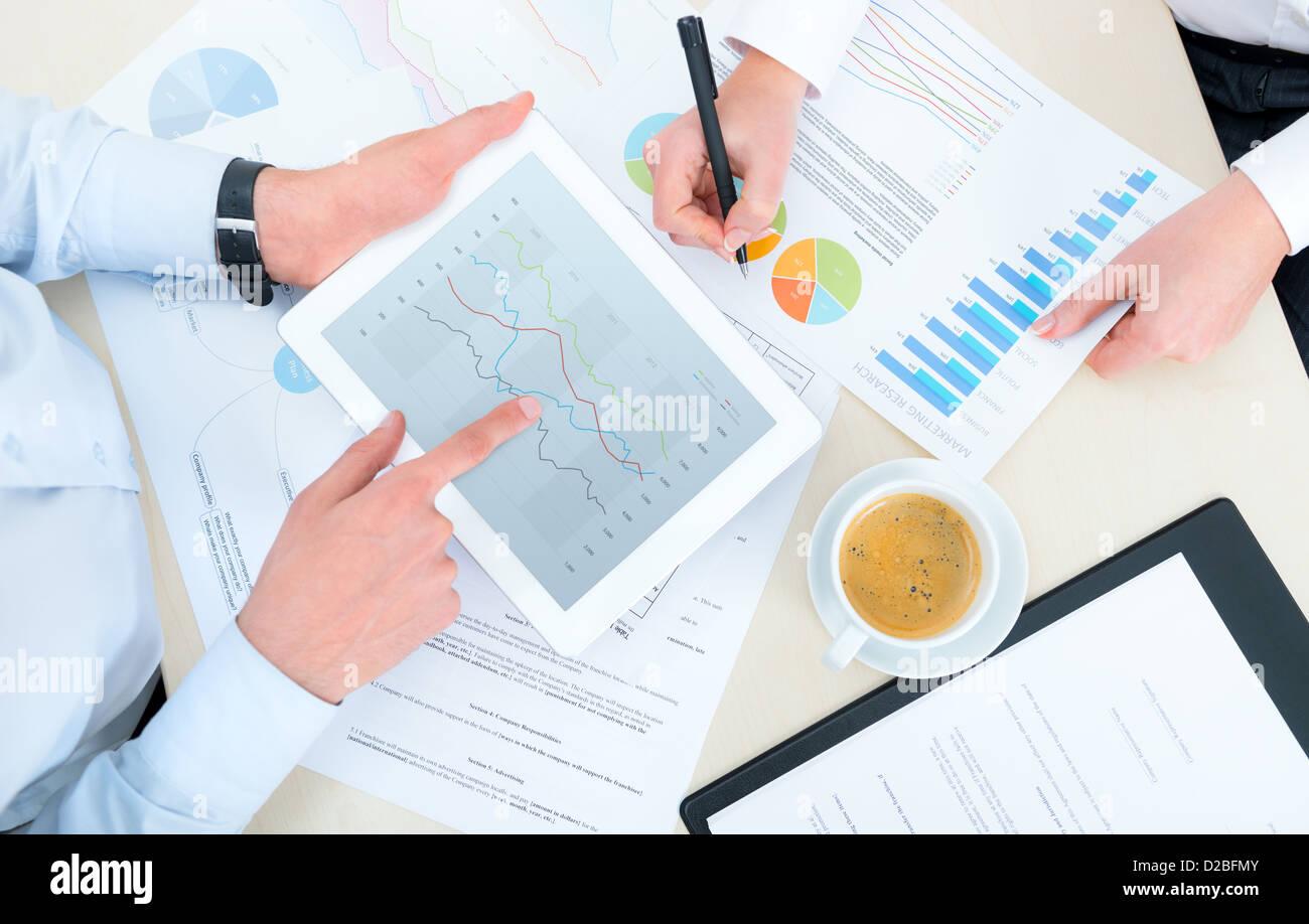 L'équipe d'analyse des tableaux et graphiques de revenu avec tablette numérique moderne. Vue supérieure Photo Stock