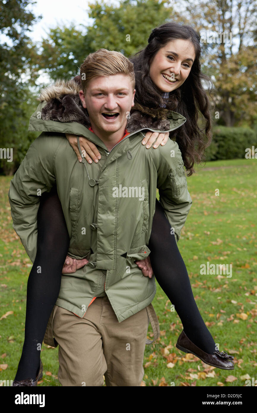 Man carrying girlfriend in park Photo Stock