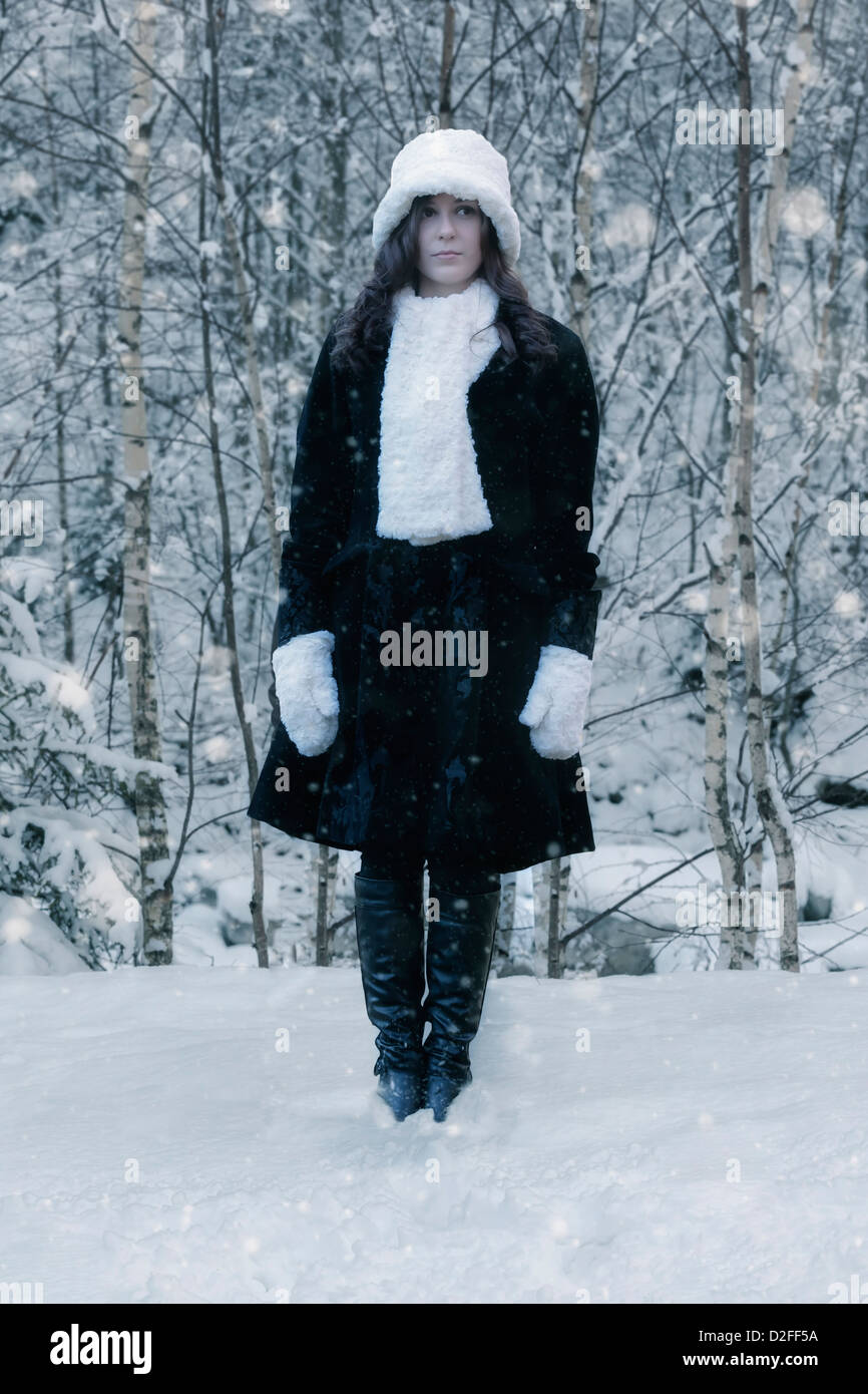 Une femme dans un manteau noir avec un chapeau blanc et écharpe blanche dans la neige Photo Stock