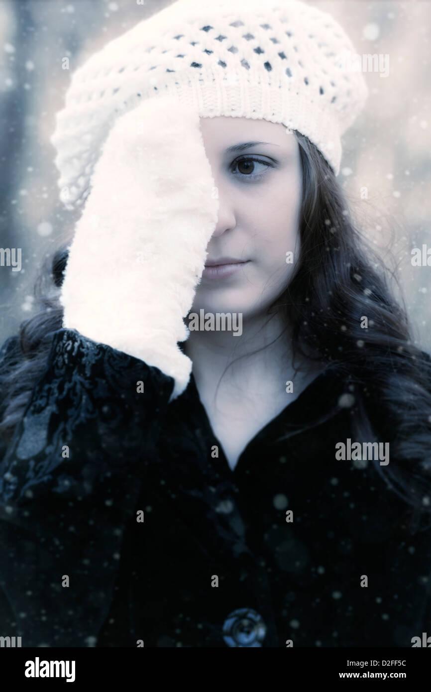 Une femme dans un manteau noir avec un capuchon blanc est la tenue d'une main gantée en face de l'un Photo Stock