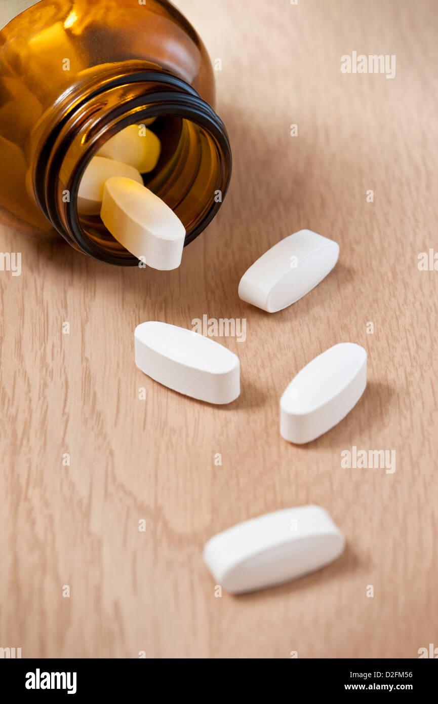 Bouteille de comprimés avec un peu de tomber sur la table Photo Stock